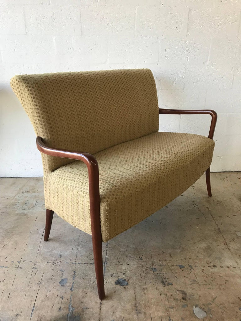 Midcentury Italian sofa settee or loveseat in the style of Paolo Buffa, walnut legs and arms, with cotton upholstery.