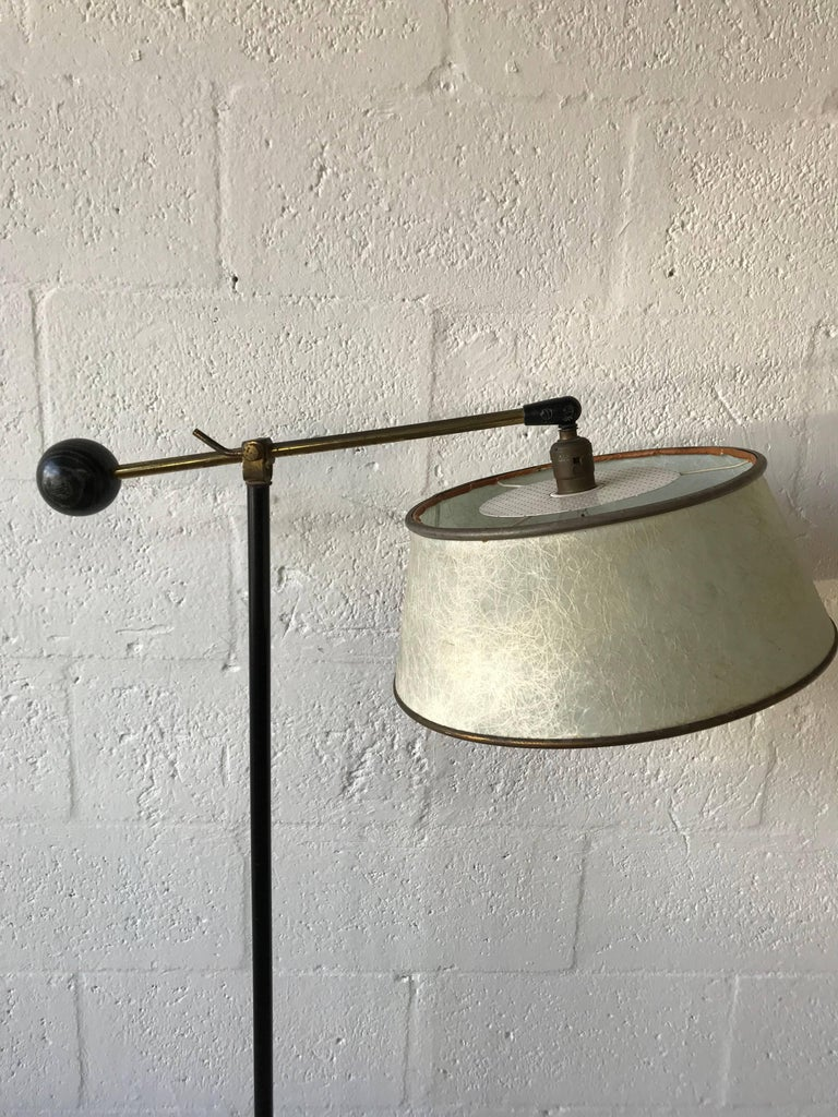 Art Deco reading or floor lamp rendered in patinated brass with an adjustable arm, original fiberglass shade with perforated diffuser and a large ebonized and cerused oak ball on the opposing side.