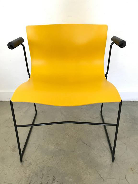 Four bright yellow sculpted dining or office chairs on a black enameled steel frame with cushion armrests by Lella and Massimo Vignelli for Knoll.