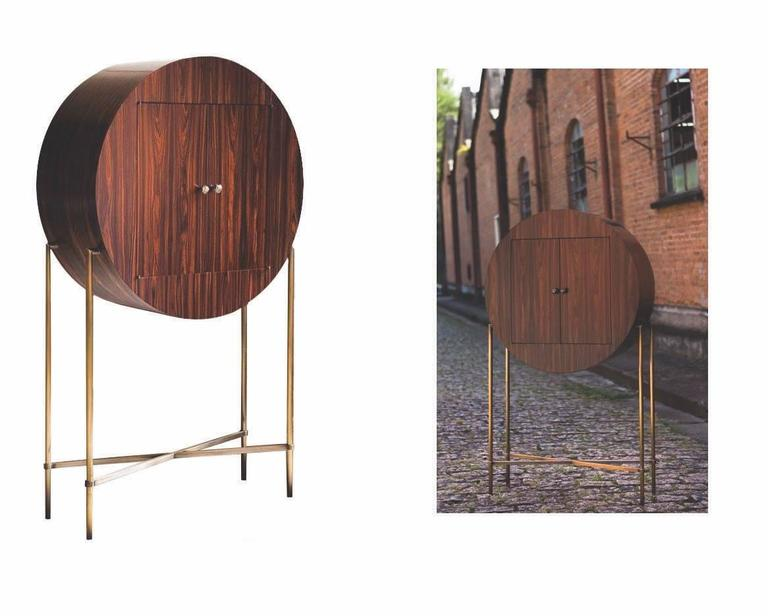 This round cabinet or dry bar is made with a Brazilian Iron wood veneer, brass legs and hand-forged brass sculpture handles by André Poli for Vermeil. It is a limited edition piece of only ten being produced, currently only six remain. Signed by