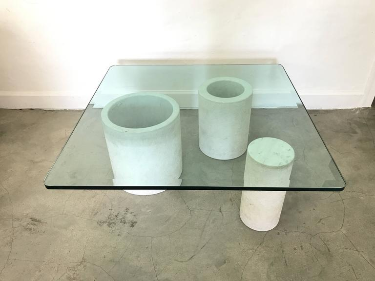 Carrara marble and half inch, beveled glass top coffee or cocktail table, Italy. Marble has a smooth, polished finish on top and inside the cylinders and the marble is etched on the exterior, style of Mangiarotti, model Loico.