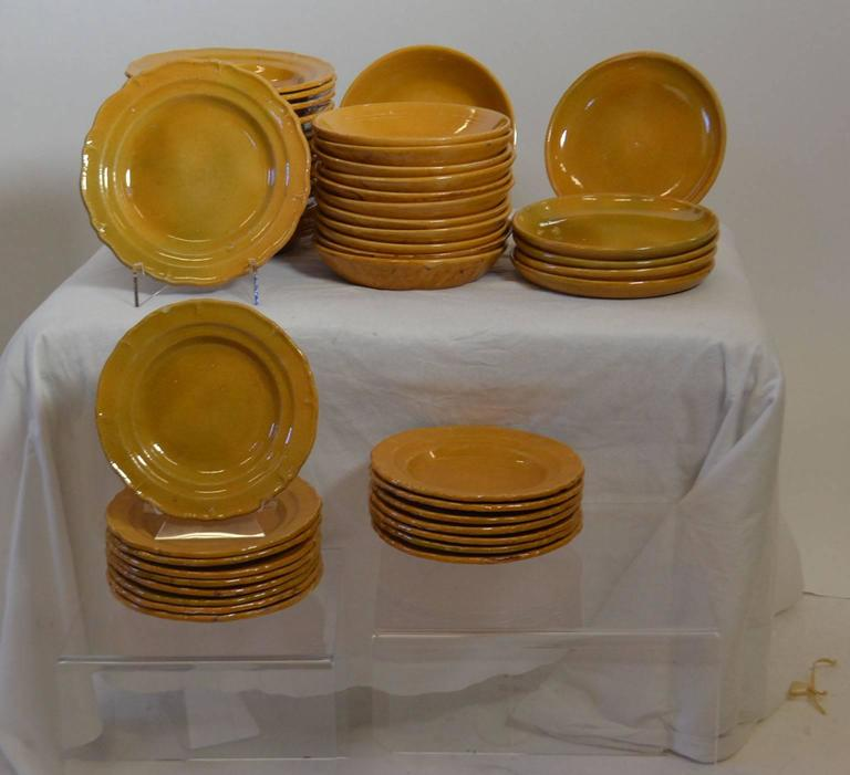 Turn of the century (circa 1900) Faience pottery tableware (56 Pieces), from the Drome area of France. Serving set (12 pieces) sold separately.  *Serving bowls three. *Misc. sized oval serving plates (5) *Small serving bowls two. *One round