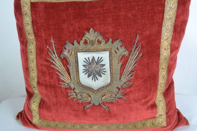 18th c. Italian crest on wine red velvet framed with vintage red and gold galon. Hand trimmed with tiny gold metallic military cording from Europe. Down filled. (THE MEWS).