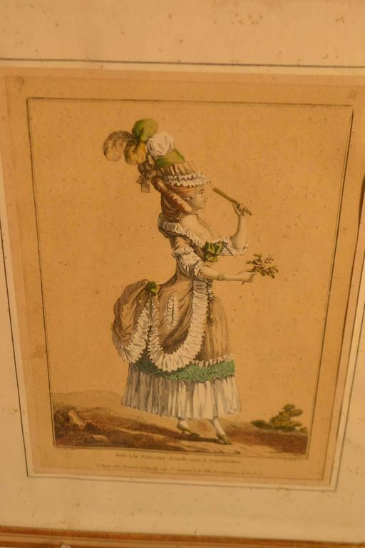 18th century framed fashion engraving of a woman dressed for entertaining or to be entertained, with a plume feather hat, a fancy bustle with green trim and a bouquet of flowers in her hand.
