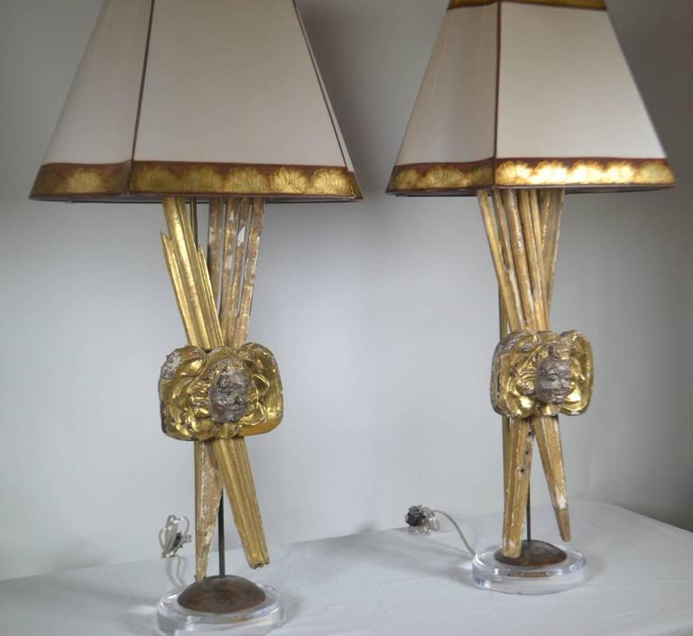 Pair of Italian 18th century giltwood pieces that are made into lamps with putti faces and sunbursts.