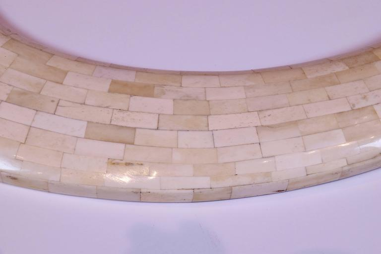 Vintage mirror with a tessellated bone frame of graduated oval form.