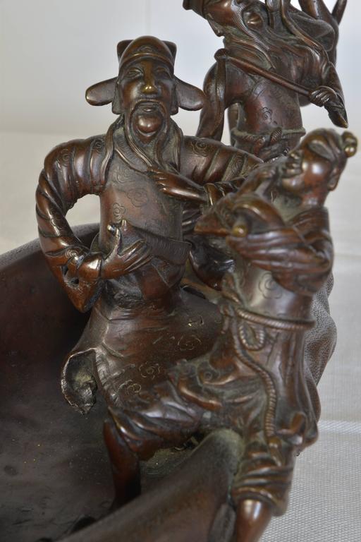 Cast Wood Art : Cast bronze sculpture of men in a boat on carved wooden