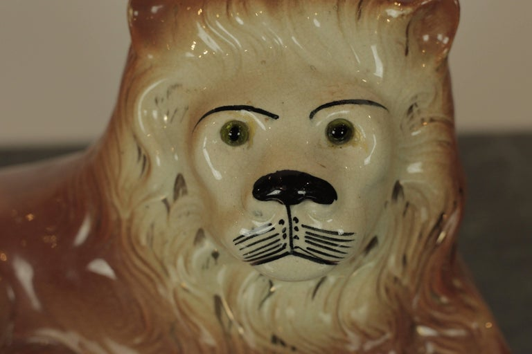 Charming Staffordshire lion in repose with green glass eyes.