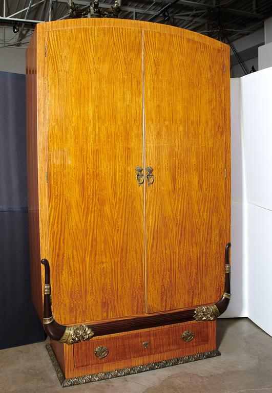 Outstanding pair of Art Deco cabinets or armoires in the manner of Sue et Mare. These examples of fine cabinet making exhibit mortise and tenon construction throughout utilizing satinwood, mahogany and ebony. The beautifully cast and chased bronze