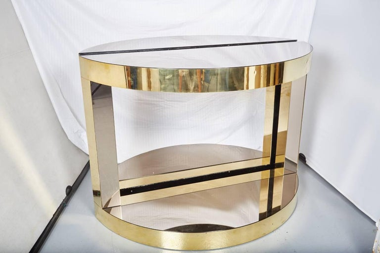Pair of midcentury Italian brass and mirrored glass demilune consoles by Sandro Petti for L Angolo Metallarte. The heavy gauge solid brass is fitted over a wood core. The mirrow glass has a smoked finish which contrasts handsomely with the polished