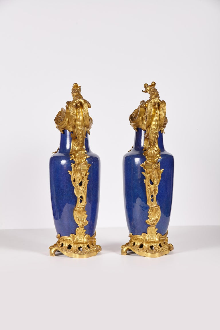 Mid-19th century powder blue Chinese vases mounted in late 19th century gilt bronze scrolls with dragon shaped handles to form ewers. The gilt bronze mounts are of superior quality workmanship.