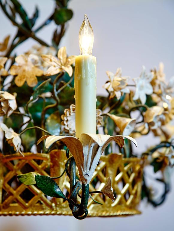 Elegant tole chandelier with antiqued white metal flowers and antiqued green foliage in a reticulated gilt metal basket. Six antiqued white lilies serve as candleholders that are wired for electricity.