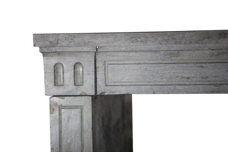 This is an 18th century blue-grey, bicolor, marble-stone original antique fireplace surround from France. It was made in the Louis XVI period. All of its pieces are solid blocks and original. The straight lines of the surround makes it perfect for