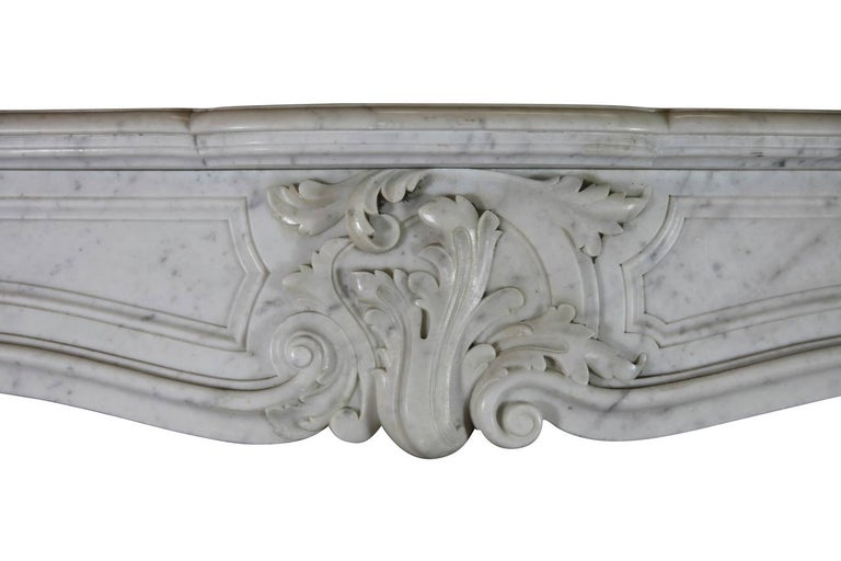 This 19th century elegant white Carrara marble original antique fireplace mantle is crafted in the Regency style. The fronton is solid and the mantle has nice proportions. It was installed in a grand Parisian apartment.  Measurements:  149 cm EW