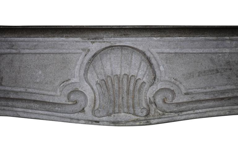 """This is a beautiful bicolored bleu-grey Burgundy hard stone fireplace surround with little remaining patina. It has a lovely shell shaped carving on the front.   Measures: 153 cm EW 60,24"""" 118 cm EH 46,45"""" 132 cm IW 51,97"""" 99 cm"""