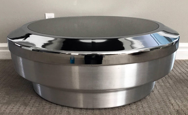A stunning round, drum/canister coffee table designed by Mastercraft in the 1970s. This stunning coffee table features a brushed chrome base, with polished chrome outer top and mirrored round top. A truly stunning piece!