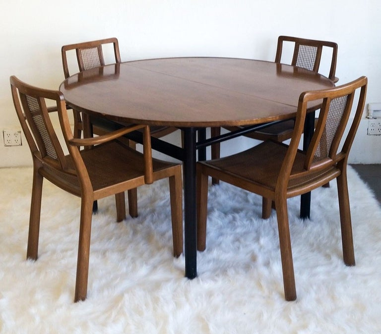 Edward Wormley for Dunbar set of 4 dining chairs and table. The set is all solid walnut with 4 cane / walnut dining chairs (One captain chair and 2 side chairs).   The set is in good condition with wear to commensurate with age. One of the seat's