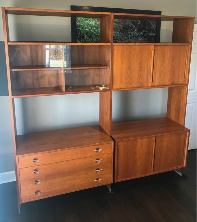 A stunning piece of Mid-Century Modern Danish design. This large teak wall unit is comprised of two large bays, with a total of four cabinets.   The wall unit is expertly constructed so that none of the drawers actually touch the floor, instead