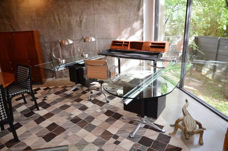 This highly innovative design by Bruce Burdick uses polished aluminum beams supported by legs with splayed cast aluminum feet to suspend glass, wood and heavy plastic composite components. This example has three work surfaces, large wood organizer,