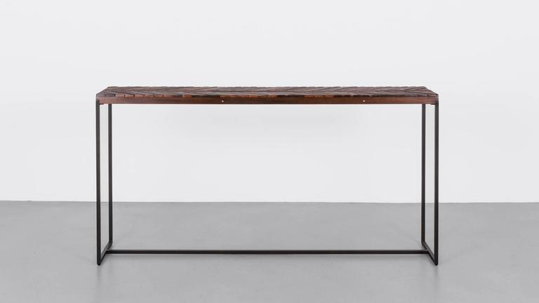 The reclaimed wood surface of our console echoes the inlaid pattern of the original boardwalk, as seen from above. The play of scale however, from the miniature nail-heads to the thinly cut Ipe, changes the context of the original design and adds an