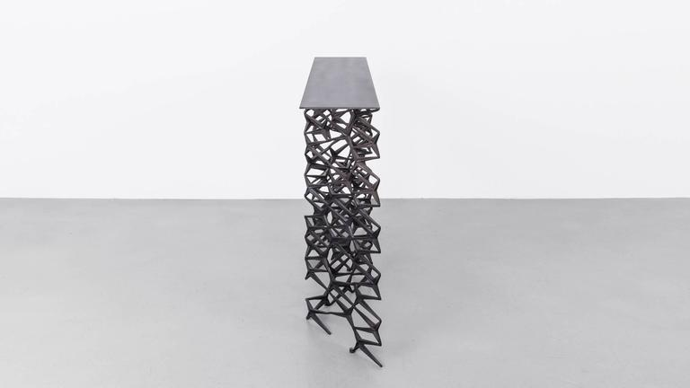 The fenced in console is made from repurposed cast-iron fence pieces in a traditional Art Deco repeat design. Originally inspired by the ornate iron work common on Brooklyn brownstones in neighbourhoods surrounding the Uhuru workshop, the fenced in