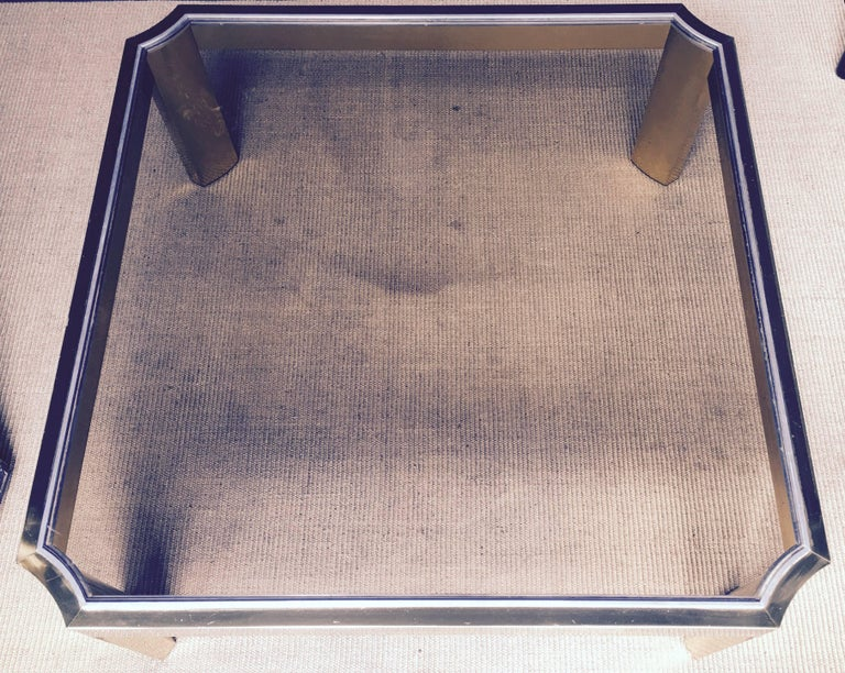 Mid-Century Modern square coffee table featuring a brushed brass plated metal frame and a removable smoked glass top. In the style of Mastercraft.