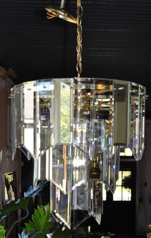 Mid-Century Modern waterfall chandelier featuring three tiers of arched/draped beveled clear glass prisms alternating with reflective mirrored glass prisms - all suspended from a brass frame.   Canopy and 13 inches of brass chain included.  Nine