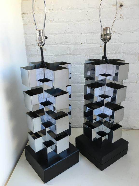 Monumental Mid-Century Modern pair of sculptural cubist table lamps by C. Jere. Each Brutalist style lamp is composed of a series of stacked chrome steel cubes. A switch on the cord illuminates a bulb within the base and top socket. Both wood lamp