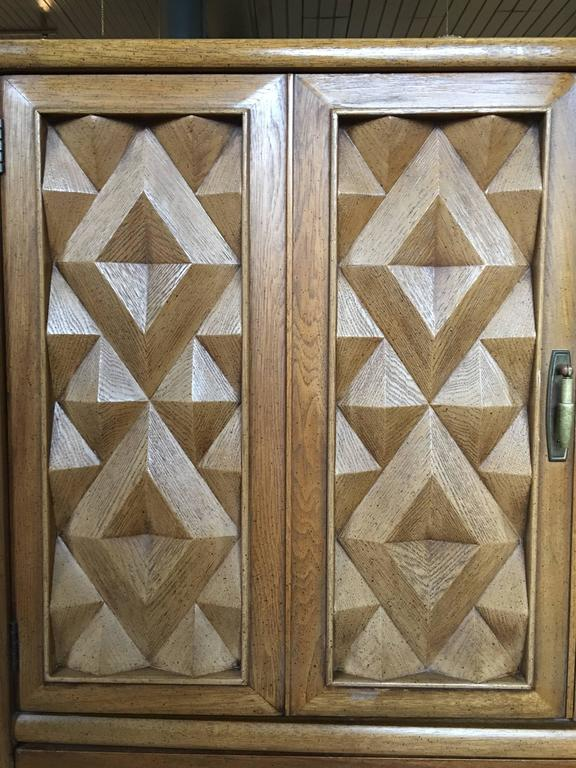 Mid-Century Modern Diamond Head armoire cabinet by Broyhill Premier. Beautiful and sculptural, this case piece features a unique geometric cubist pattern in natural pecan tones and original brass hardware. This brutalist style chest can be used as a