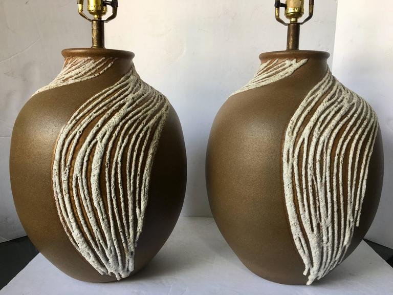 Sizable pair of Mid-Century Modern lava glazed drip pottery table lamps. Matte brown tone ceramic glazed bases feature a white dimensional lava/volcanic textured drip glaze.  Measures: Height to harp 32 inches high. Height to socket 22 inches