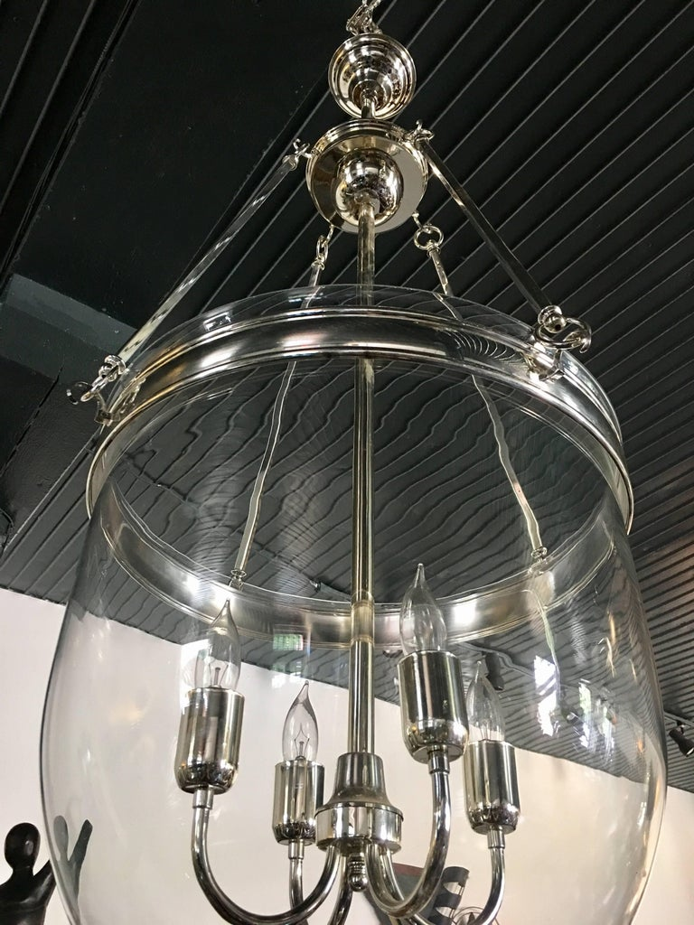 Large glass and polished chrome hurricane dome pendant light fixture. Removable clear glass bell jar is suspended from four square rods. Centre holds four standard base candle bulbs.  Measure: Height is adjustable. Length of fixture from bottom