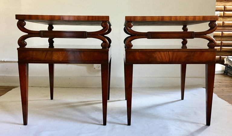 Midcentury Regency style two tier side tables from Weiman's Heirloom collection. Mahogany wood frames feature carved scroll details, gold scribed brown leather tops, and tapered legs. Stamped