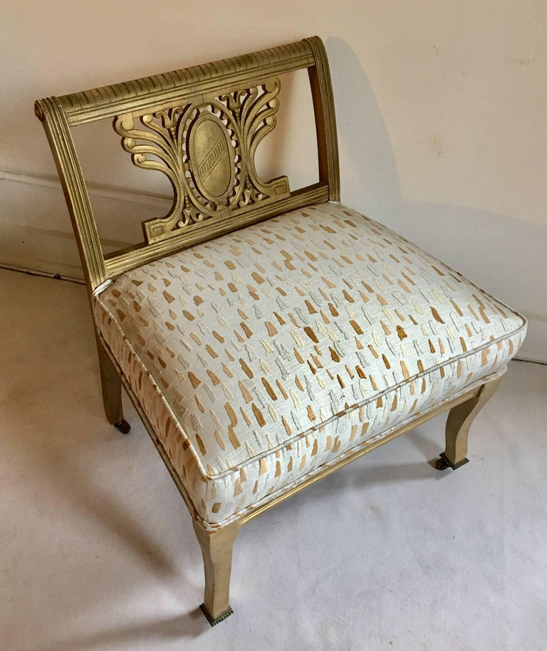 Mid-Century carved wood vanity chair or bench newly upholstered in Laura Kirar/Highland Court geode metallic thread fabric. Chair frame features a carved crest or shield back, scrolled details with Greek key motif and original aged gilt painted