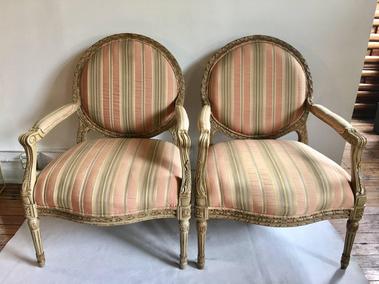 Pair of vintage French XVI style bergère armchairs by Henredon Fine Furniture. These generous sized accent chairs feature carved relief painted wood frames with a traditional round medallion shaped back and neoclassical style fluted legs. Chairs are