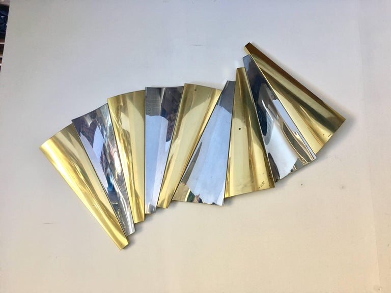 Modern brass and chrome wall sculpture by Curtis Jere. This mixed metal abstract art sculpture features a curved fan-like design. Can be hung in multiple ways or angles. Signature no longer visible due to cleaning.