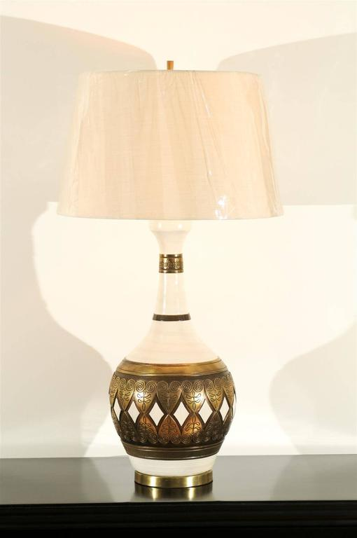 A spectacular pair of large-scale vintage lamps by Fortune Lamp Company, circa 1961. Cream ceramic vessels with fabulous gold detail which portrays the look of genuine forged brass. Remarkable design and craftsmanship. This small boutique lighting