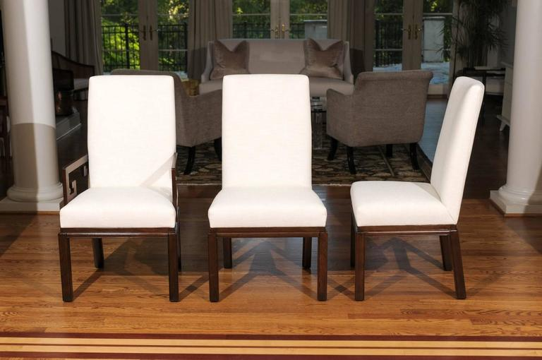 A sublime set of ten (10) restored Parsons style dining chairs by Baker, circa 1970.  This elegant series is routinely attributed to the esteemed Michael Taylor.  Beautiful, expertly crafted walnut construction. Host chairs with Greek Key arm