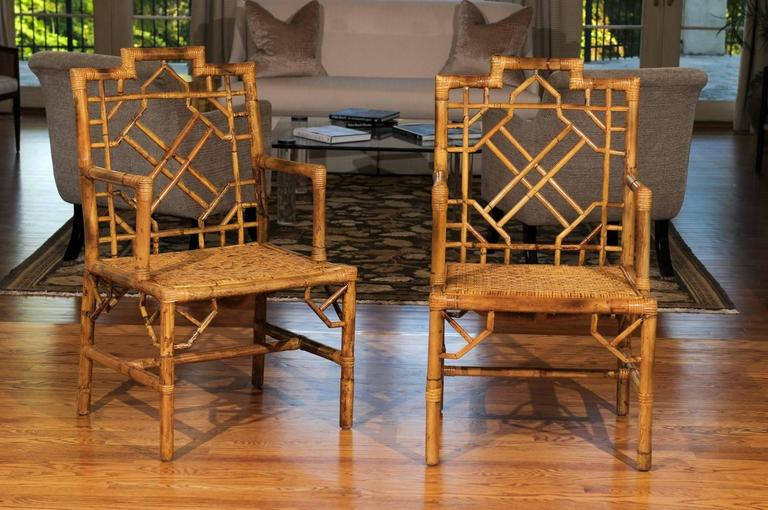 A lovely pair of vintage armchairs, circa 1970. Exceptional rattan construction in the Chippendale style with raffia seats. Stout, highly decorative pieces that also offer great comfort. The pair will also serve as wonderful host dining chairs.