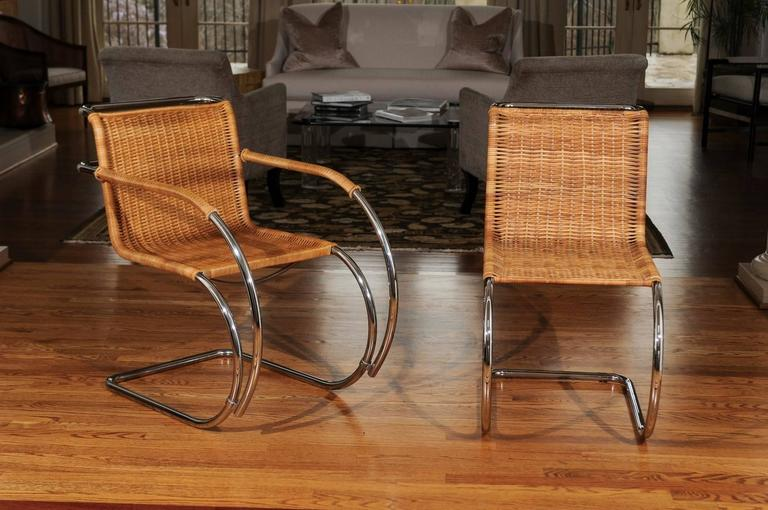 A fabulous set of eight vintage wicker and chrome dining chairs in the style of Mies van der Rohe, circa 1970. Stellar quality and craftsmanship. This coveted cane version is always difficult to find and next to impossible to locate in exceptional