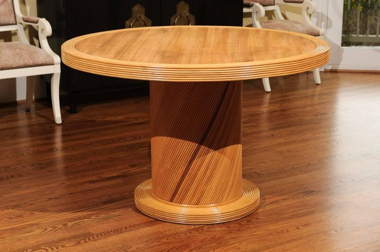 A beautiful vintage pedestal center or dining table by Bielecky Brothers, circa 1980. Stout solid hardwood form veneered in pencil bamboo. Lovely cane raffia inset top. Exceptional quality and craftsmanship. Stunning warmth, texture and range of