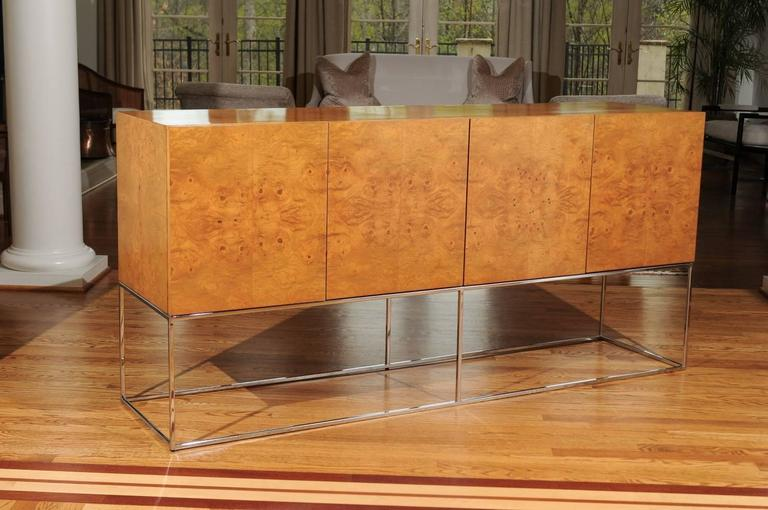 A stellar buffet or credenza by Milo Baughman for Thayer Coggin, circa 1975. Exquisite bookmatched olivewood veneer over solid ash case construction atop an elegant chrome base. Tremendous craftsmanship and attention to detail. This particular