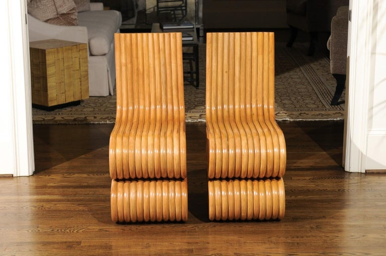 A unique set of eight stunning custom made dining chairs, circa 1995. This particular rattan design was undoubtedly inspired by the groundbreaking Frank Gehry Wiggle chair series of the early 1970s. This fabulous set was custom commissioned for the