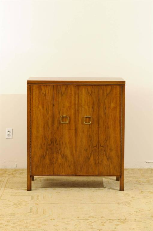 An beautiful modern multipurpose cabinet by John Widdicomb, circa 1960. A stout and expertly made piece with sublime bookmatched black walnut veneer and lovely solid brass hardware. A functional piece that may be utilized as a chest or a