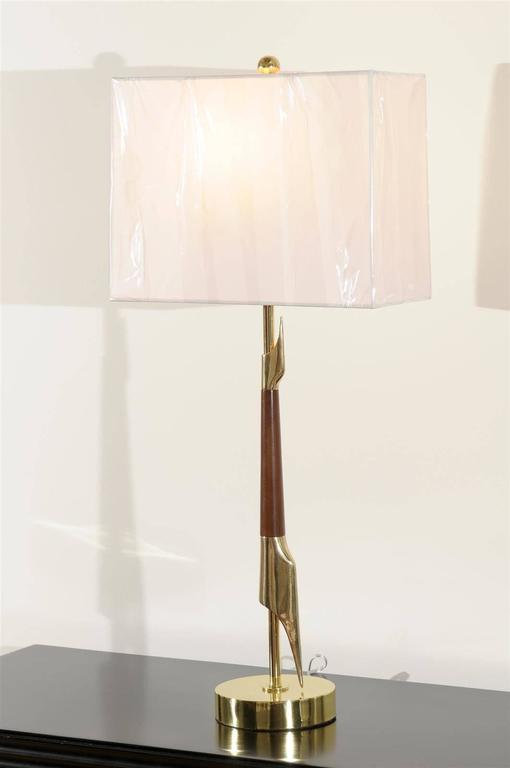 An exquisite pair of lamps from a difficult to find series by Rembrandt, circa 1960. A tall, elegant modern design executed in walnut and brass. Fabulous Jewelry! Excellent restored condition. Rewired using clear cord, new brass three-way sockets