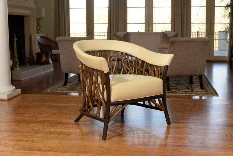 A fabulous organic pair of lounge or club chairs by Palecek. Handsome barrel back design with a beautiful vine-like rattan detail. Stout and exceptionally made pieces. The chairs have been custom upholstered in a rich parchment colored leather.