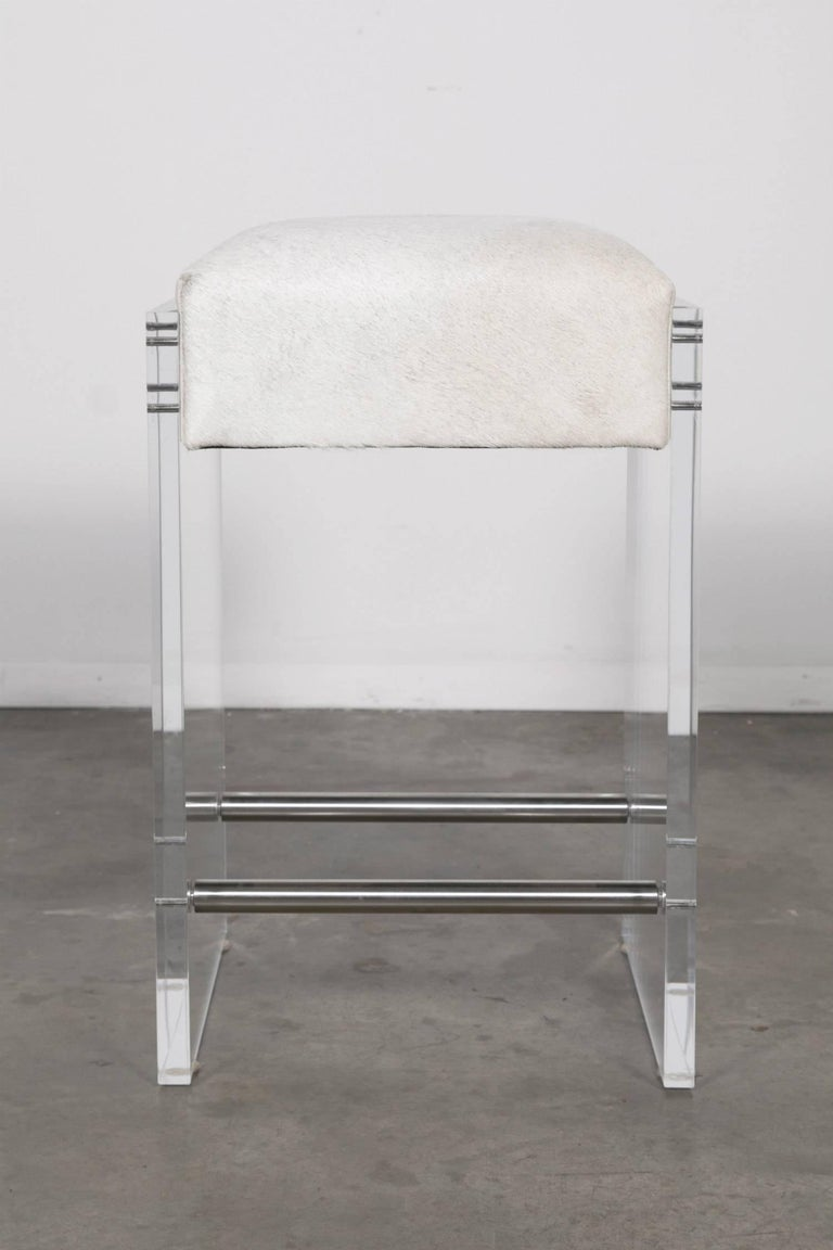 Gigi Lucite counter stool with two stainless foot rests. Add style and a touch of Hollywood Glam to your decor. Modern acrylic frame fastens to cowhide seat featuring cream faux leather sides with polished stainless steel fasteners. Counter stool