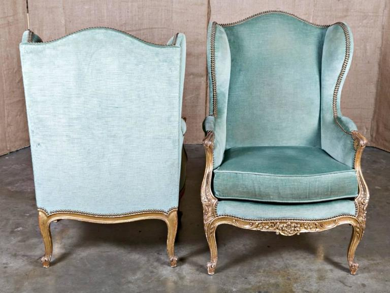 Pair of exceptional 19th century French Louis XV style carved giltwood bergère à oreilles (wingbacks,) having chapeau de gendarme backrests with extending wings upholstered in velvet with brass nailhead trim. Down filled cushions flanked by