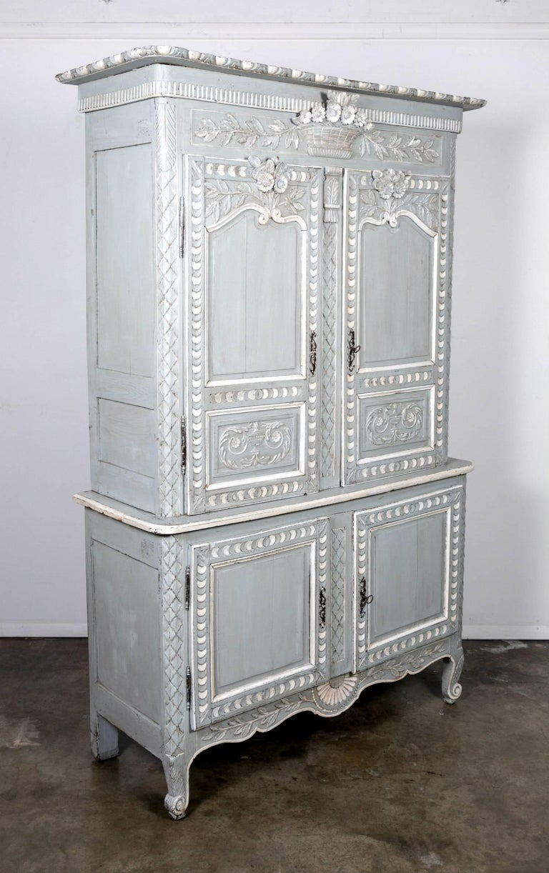 A charming painted Country French Louis XV style marriage buffet deux corps from Normandy, having a large flat, molded cornice sitting atop a carved upper frieze embellished with foliage and flowers in carved relief, as well as offering