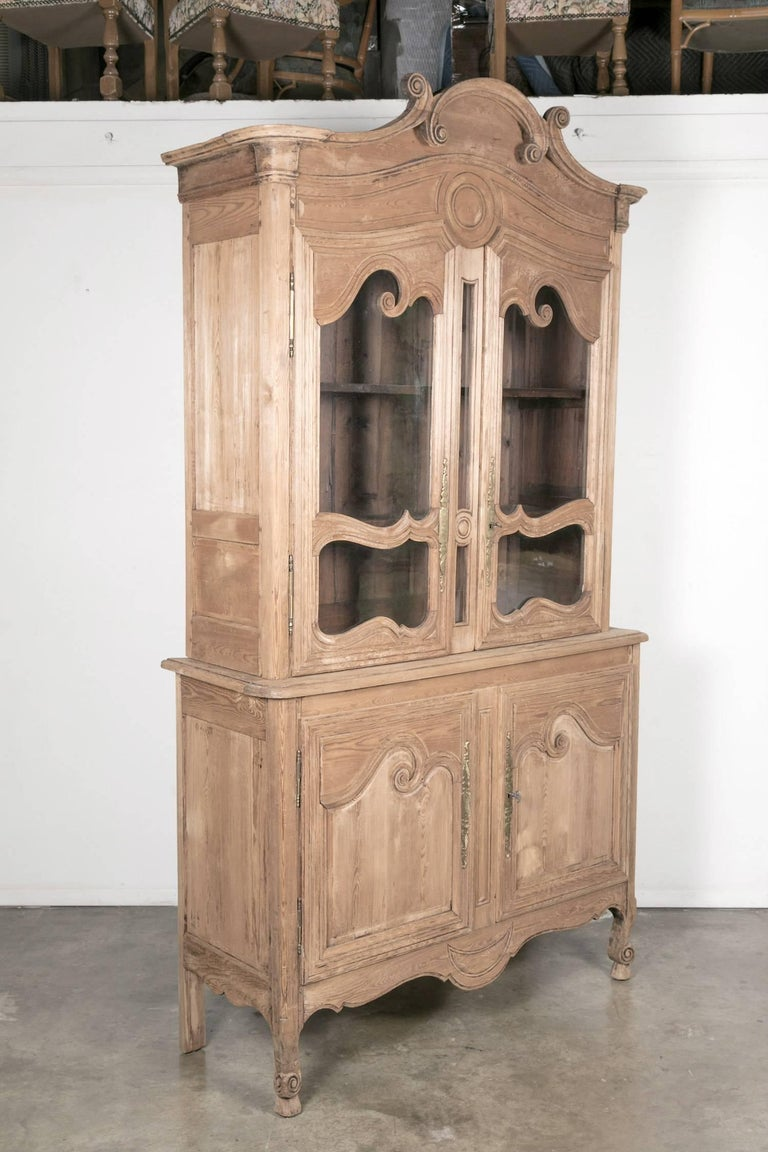 19th century French Louis XV style bleached or washed oak buffet deux corps handcrafted from French pitch pine by skilled artisans of Pays de Caux, Normandy. Upper cabinet with chapeau de gendarme crown with C-scrolls above a carved frieze decorated
