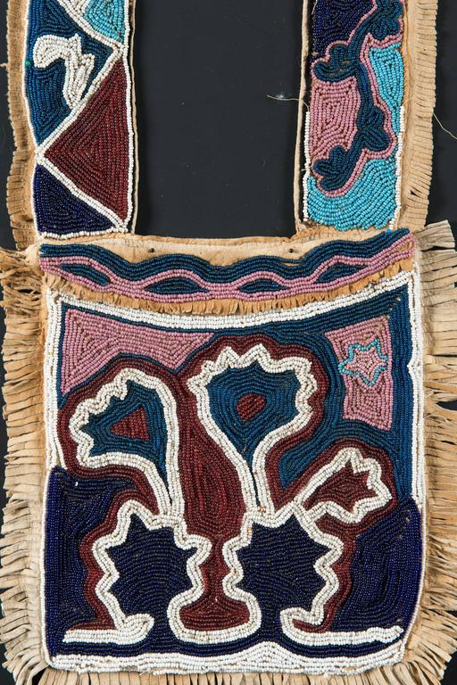 """Region / Tribe: Oklahoma territory Delaware / Creek-Cherokee,  circa 1860s  Material: Native tanned deer hide, cotton thread, glass beads  Dimension: L. 34"""" x W. 10"""" (bag), W.of bandolier with fringe 3""""   Collection History: Private"""